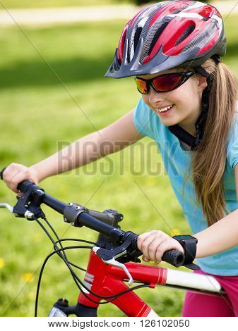 Bikes cycling girl rides bicycle on green grass in park outdoor.
