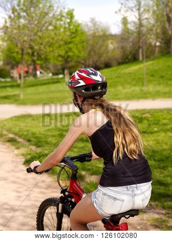 Bikes cycling girl wearing helmet ride on road into park.
