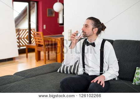 Bearded Man In White Shirt With Bow-tie Drinking Water