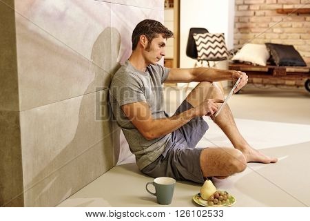 Casual man sitting on floor at home, using tablet computer. Side view.