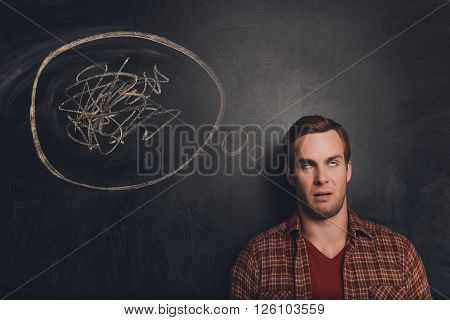 Young Freelancer At A Loss On The Background Of Chalkboard