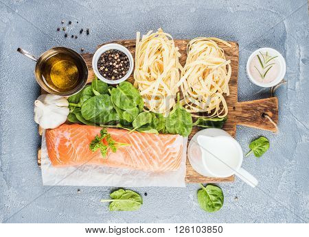 Ingredients for cooking pasta tagliatelle with salmon, spinach and cream on rustic wooden board over grey concrete textured background, top view, horizontal