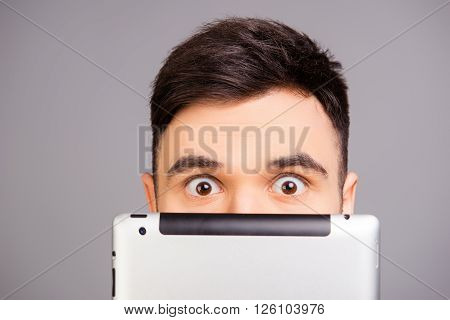 Close Up Portrait Of Young Man Hiding His Face Behind Tablet
