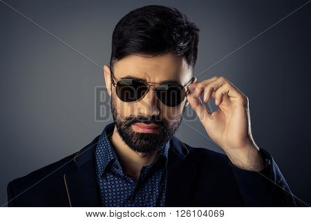 Portrait Of Trendy Man In Suit Touching His Spectacles