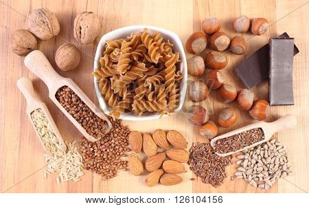 Fresh ingredients and products containing magnesium and dietary fiber healthy food and nutrition wholemeal pasta buckwheat brown rice linseed sunflower almonds hazelnut walnut chocolate