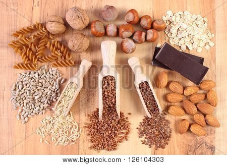 Fresh natural ingredients and products containing magnesium and dietary fiber healthy food and nutrition wholemeal pasta sunflower buckwheat brown rice linseed almonds chocolate oatmeal hazelnut walnut