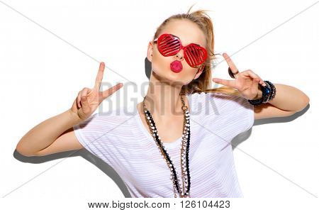 Fashion Model girl isolated over white background. Beauty stylish blonde woman posing in fashionable clothes and heart shaped sunglasses. Casual style with beauty accessories. High fashion urban style