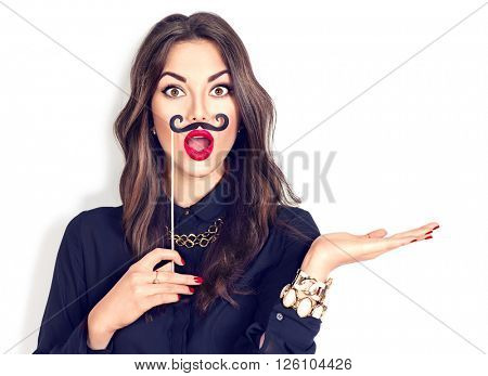 Surprised model Gil holding funny mustache on stick and showing empty copy space on the open hand palm for text, white background. Happy girl presenting point. Proposing product. Advertisement gesture