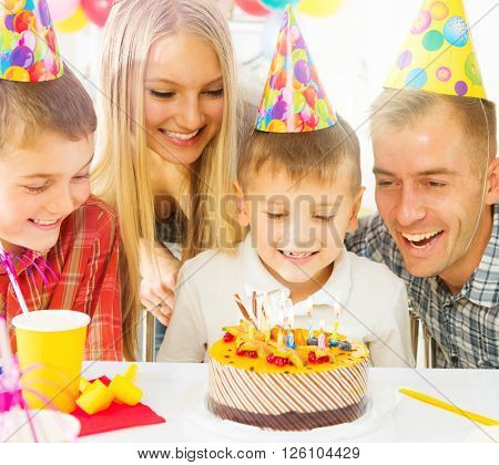 Birthday kids party. Happy big family celebrating birthday of kid. Little boy blows out candles on birthday cake at party, Children having fun