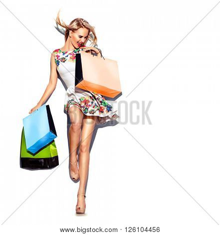 Fashion Shopping Sexy Model Girl full length Portrait. Beauty Woman with Shopping Bags in short white dress isolated on White. Blowing blond hair, high hills. Shopper. Sales