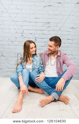 Young Couple In Love Sitting On The Floor And Looking On Each Other