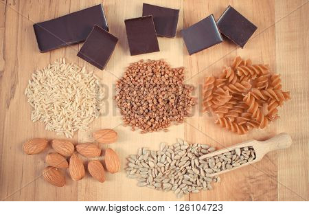 Vintage photo  Natural ingredients and products containing magnesium and dietary fiber healthy food and nutrition wholemeal pasta buckwheat brown rice sunflower almonds chocolate