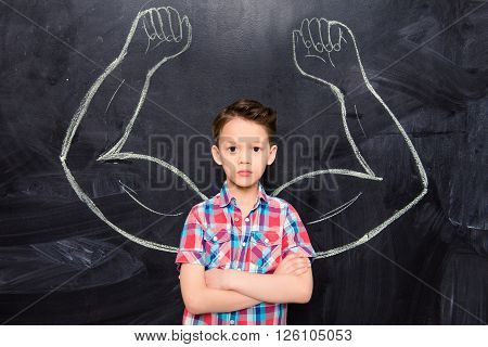 Little Boy On Backgroung Of Blackboard With Drawn Muscles