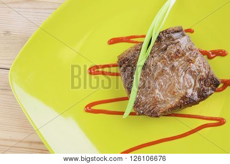 meat food : roast beef fillet mignon served on green plate with chives and ketchup over wooden table