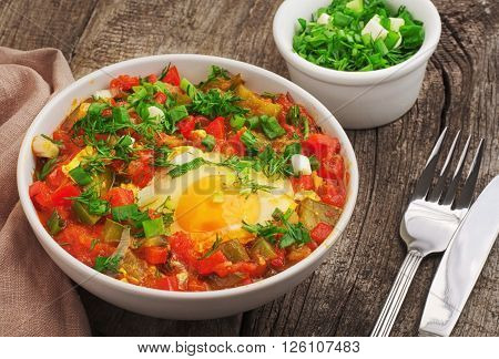 Shakshuka with tomatoes and eggs in white bowl on a wooden table close-up. Healthy food