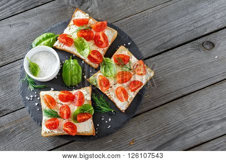 Tomato and cheese bruschetta on a ceramic cutting board top view with copy space. Healthy breakfast