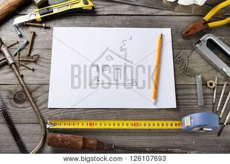 Old tools on a wooden table in the workshop with a picture of house on a piece of paper top view