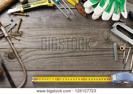 Old tools on a wooden table in the workshop with space for your text top view