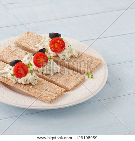 Dry diet crisp breads with cheese cherry tomatoes and olives on wooden background. Delicious and healthy food. Square frame ** Note: Soft Focus at 100%, best at smaller sizes