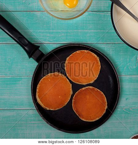 pan with pancakes and ingredients for making pancakes on a light in a rustic wooden background top view. Square frame