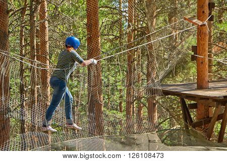 Girl going through obstactles in Rope Forest amusement park