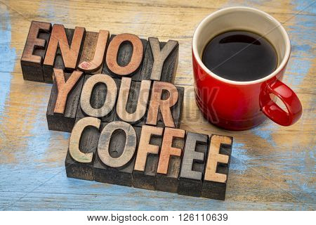 enjoy your coffee  - text in vintage letterpress wood type printing blocks with a cup of espresso coffee