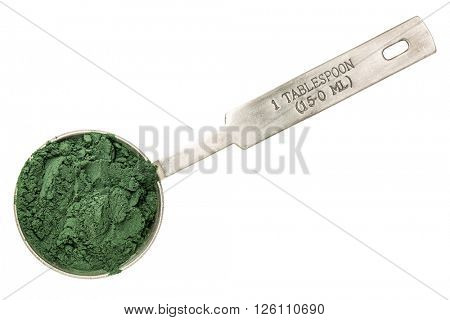 Nutrient-rich organic blue green algae  powder - isolated measuring metal tablespoon, top view