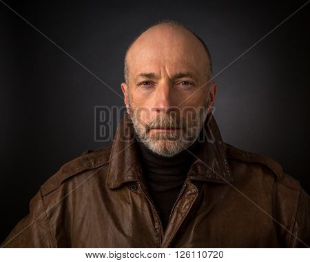 serious and focused senior man in leather jacket - a headshot against a black background