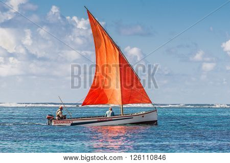 Blue Bay Mauritius - December 28 2015: The boat with a red sail in Indian Ocean - Beautiful sea scene in Blue Bay Mauritius.