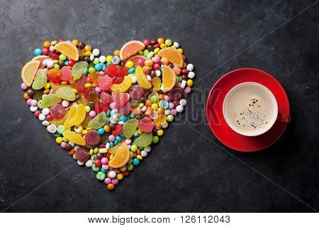 Colorful candies, jelly and marmalade heart and coffee cup on stone background. Top view