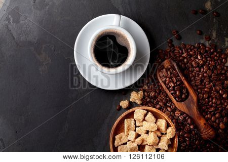 Coffee cup, beans and brown sugar on stone table. Top view with copy space