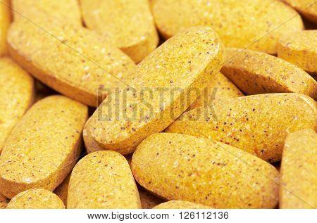 Yellow pills heap, close up