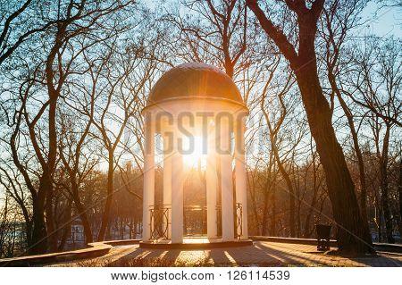 Sun at sunset shining through gazebo in city park in Gomel, Belarus. Garden pergola. Lens flare effect.