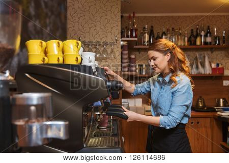 equipment, coffee shop, people and technology concept - barista woman making coffee by machine at cafe bar or restaurant kitchen