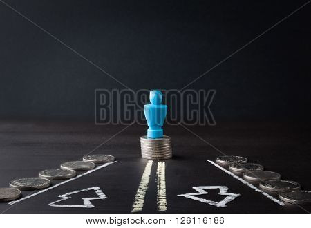 Male Figurine Standing On Pile Of Coins