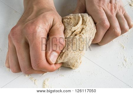 Close up image of a woman' s hands kneading dough on a table.