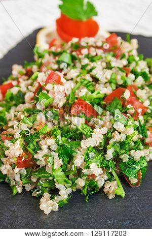 Colorful tabbouleh salad with quinoa, parsley and tomatoes.