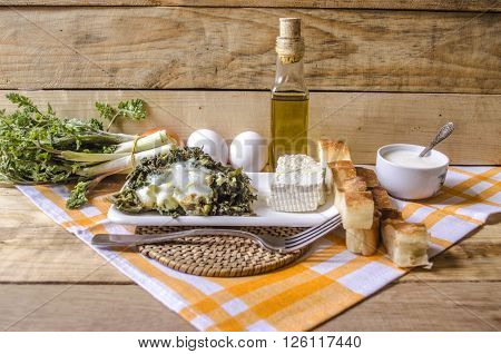 Shoots of edible spring grass, sour milk and sheep's cheese on the rough wooden boards covered with kitchen towel