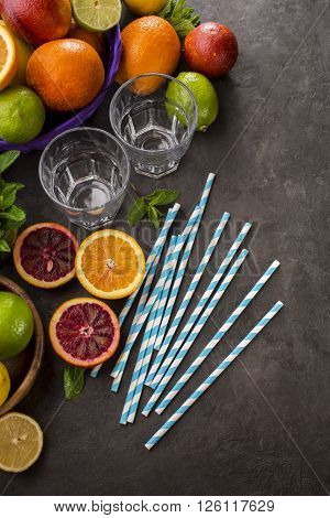 Refreshing summer cocktails with Oranges limes and lemons. Citrus fruits glass straws and mint over dark background