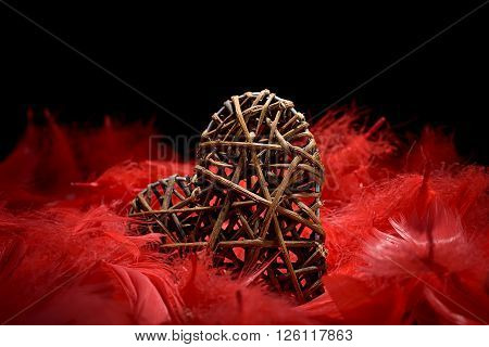 wooden heart in the midst of red feathers