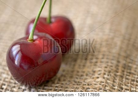 macro two red cherry fruit on jute