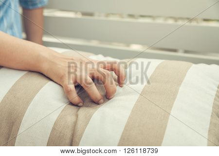 Woman hand grasp pillow sheet, vintage filtered image.