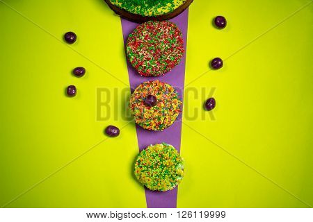 multicolored sweet easter gingerbread cakes round shapes sugar candies around bright yellow purple kitchen background celebration photography
