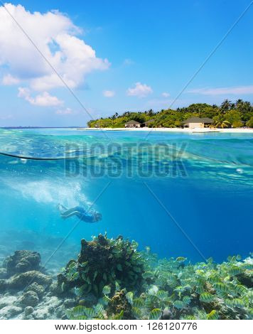 Young woman diver exploring coral reef