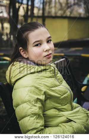 Girl teenager in a green jacket sits on a bench in the park