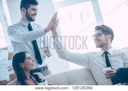 Give me high-five! Two handsome man giving high-five and holding coffee cups with smile while sitting on the couch at office with their beautiful coworker