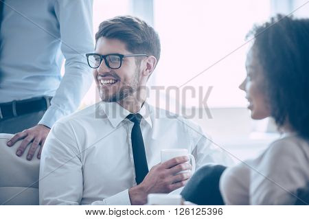 Life of businessman. Close-up part of young handsome cheerful man holding coffee cup and looking away with smile while sitting in office with his coworkers