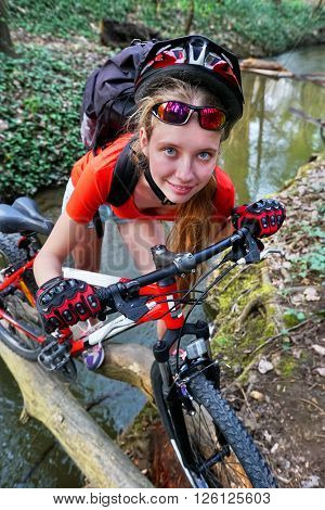 Bikes cycling girl cycling fording throught water on log .