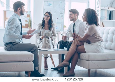 Sharing good news. Young handsome man gesturing and discussing something with his coworkers with smile while sitting on the couch at office
