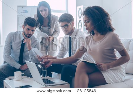 Take a look at this statistics! Young beautiful African woman pointing at her laptop while sitting on the couch at office with her coworkers